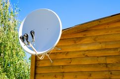 Satellite antenna. On a wooden house outdoors royalty free stock photography