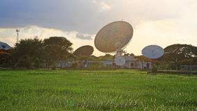 Satellite communication dish against flare light Royalty Free Stock Images