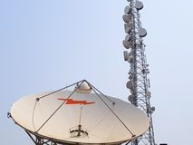 Satellite communications dish, with a cell tower in the background stock photos