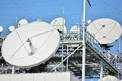Satellite Communications Dishes on top of TV Station. Satellite dish antenna on top of the building royalty free stock image