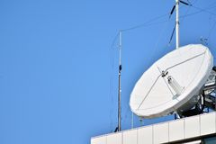 Satellite Communications Dishes on top of TV Station. Satellite dish antenna on top of the building stock photography
