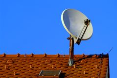 Satellite dish. A white satellite dish on red roof royalty free stock photo