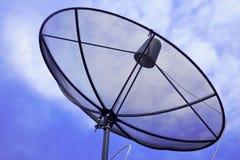 Satellite dish. Black satellite dish on blue sky background stock image