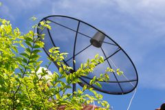 Satellite dish. Black satellite dish  on the roof under blue sky Stock Images