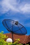 Satellite dish. Black satellite dish on the roof under blue sky stock images