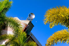 Satellite dish. On top of a university building with brilliant blue sky the moon and palm trees adorning the landscape around the building Stock Images