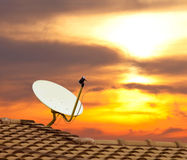 Satellite dish. With sunset on roof Royalty Free Stock Photo