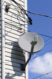 Satellite dish. On a wall of a typical American house Royalty Free Stock Photo