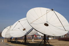 Satellite dish. White satellite dish under clear blue sky Royalty Free Stock Images