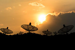 Satellite dish. Against silhouette mountain with sunset background royalty free stock photo