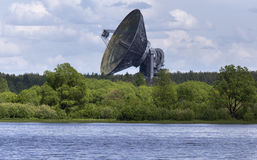Satellite dish aimed at the sky. Huge satellite dish aimed at the sky, stands near river bank in Kaljazin, Russia Stock Image