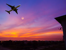 Satellite dish with airplane and moon in sunset sky. Stock Photo