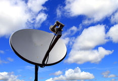 Satellite dish antenna. Closeup shot of satellite dish antenna against cloudy blue sky Stock Image
