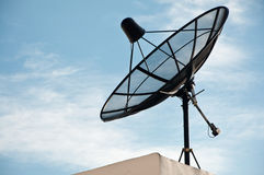 Satellite Dish Antenna. Satellite dish on top of the building with clear sky in the background Stock Photo