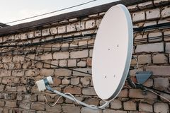 Satellite dish antenna on brick wall at building Stock Photo