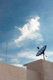 Satellite Dish Antenna and lighting rod. Satellite dish on top of the building with clear sky in the background with lighting rod Royalty Free Stock Photography