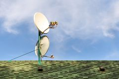 Satellite dish antennas on rooftop of private house covered with shingle tile. Blue sky on bright sunny day on stock photo
