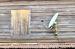 Satellite dish is attached to the old wooden house. Urban  in Thailand Royalty Free Stock Image