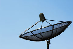 Satellite dish. Black dish mounted on a rooftop against clear blue sky Royalty Free Stock Images