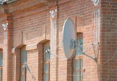 Satellite dish on a brick wall. Stock Photos