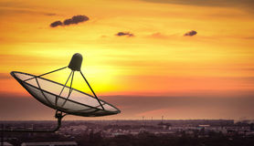 Satellite dish in the city on sunset. Stock Photos