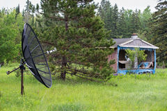 Satellite Dish in Front of an Abandoned House or Shack Royalty Free Stock Photo