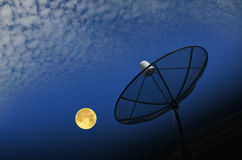 Satellite dish and full moon with white clouds Stock Photo