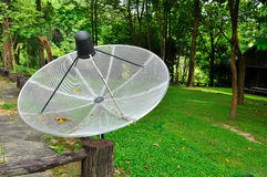 Satellite dish in the garden Royalty Free Stock Photo