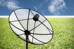 Satellite dish on the grass and blue sky. Stock Images