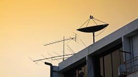 Satellite dish and old fishbone tv antenna Stock Image