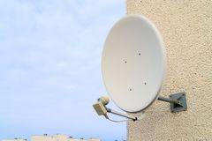 A satellite dish for receiving TV signal is bolted to the white wall. Russia residential sector stock photography