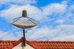 Satellite dish on red roof. With clouds royalty free stock images