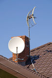 Satellite dish on the roof. White satellite dish on brown roof Royalty Free Stock Images