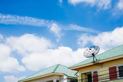 Satellite dish on the roof with a blue sky background. Satellite dish on the roof with a blue sky background in villege Stock Image