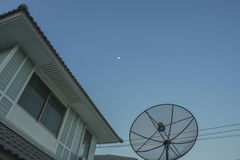 Satellite dish on the roof. Blue sky with part of the moon Royalty Free Stock Images