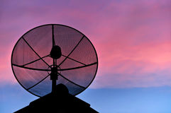Satellite dish on the roof in evening sky. Royalty Free Stock Photography