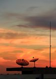 Satellite dish on the roof at sunset with golden c. Satellite dish on the roof at sunset Royalty Free Stock Photos