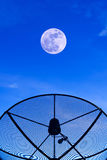 Satellite dish on the roof with supermoon night sky background. Stock Photos