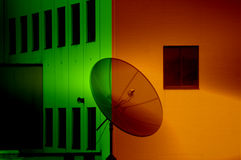 Satellite Dish Silhouette Against Colorful Building Stock Image