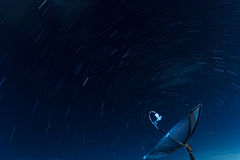 Satellite Dish and Star Trails. Blue sky Royalty Free Stock Photo