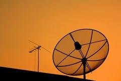 Satellite dish in sunset. Black antenna communication satellite dish in sunset sky Stock Images