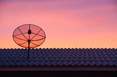 Satellite dish in sunset sky. Silhouetted satellite dish on the roof in sunset sky Stock Photo
