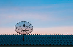 Satellite dish in sunset sky. Silhouetted satellite dish on the roof in sunset sky Royalty Free Stock Photography