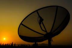 Satellite dish on sunset sky background. Royalty Free Stock Photo