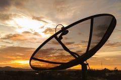 Satellite dish on sunset sky background. Stock Photos
