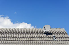 Satellite dish on tiled roof Stock Photo