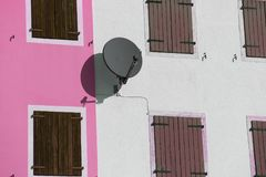Satellite dish to receive satellite TV programs on the wall. Of an house Royalty Free Stock Photo