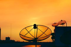 Satellite dish on top of building with sky sunset digital television stock image