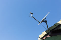 Satellite dish and TV antennas on the house roof Royalty Free Stock Photography