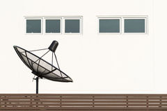 Satellite dish TV antennas beside house. On the second floor Stock Image
